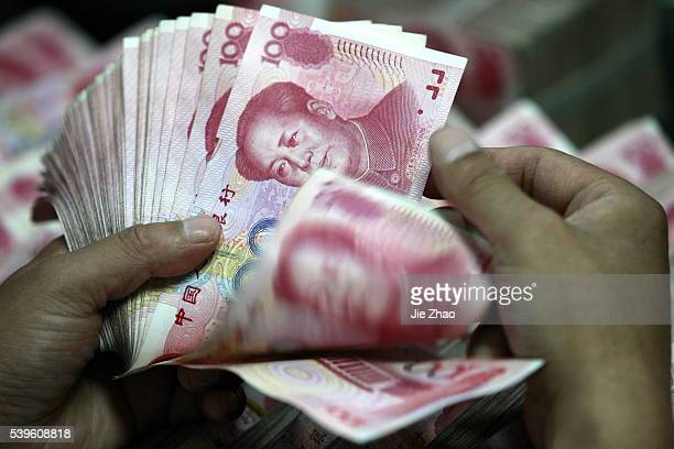 A Chinese bank clerk counts RMB yuan banknotes at a bank in Huaibei east Chinas Anhui Province July 6 2012