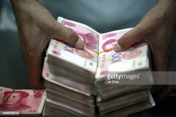Chinese bank clerk counts RMB yuan banknotes at a bank in Huaibei, east Chinas Anhui Province, July 6, 2012.