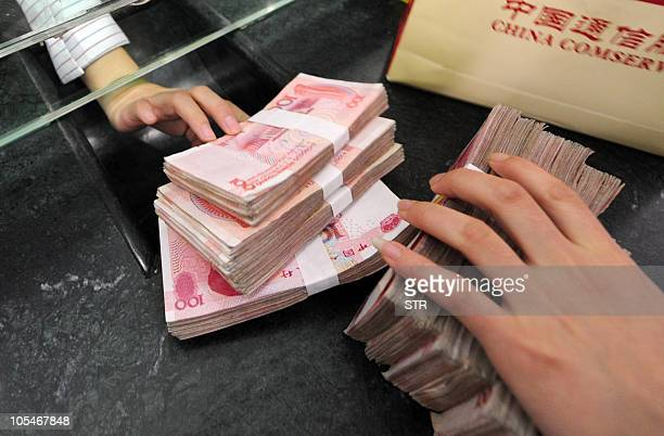 A Chinese bank clerk receives the stacks of onehundred yuan notes for a customer at a bank in Hefei east China's Anhui province on October 14 2010...