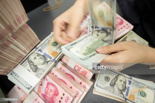 Chinese bank employee counts 100-yuan notes and US dollar bills at a bank counter in Nantong in China's eastern Jiangsu province on August 6, 2019. -...