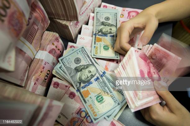 A Chinese bank employee counts 100yuan notes and US dollar bills at a bank counter in Nantong in China's eastern Jiangsu province on August 28 2019...