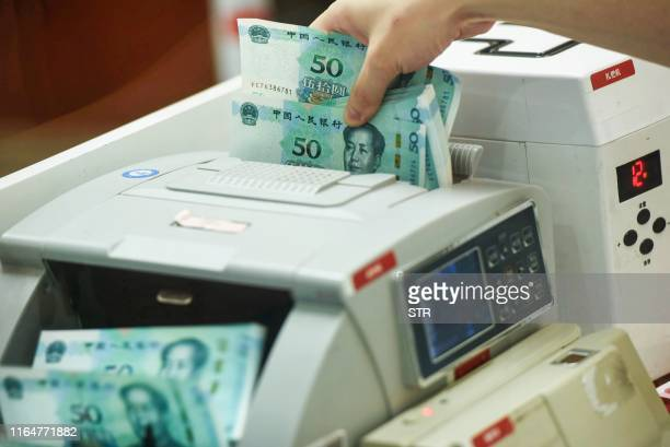 Chinese bank employee counts new 50-yuan notes with a money counting machine at a bank counter in Hangzhou in China's eastern Zhejiang province on...
