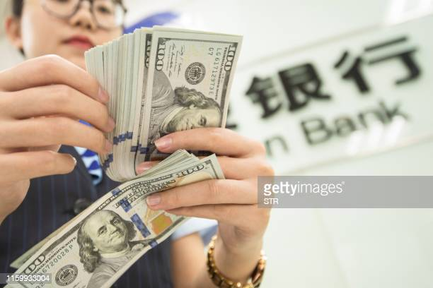 Chinese bank employee counts US dollar bills at a bank counter in Nantong in China's eastern Jiangsu province on August 6, 2019. - The Chinese...
