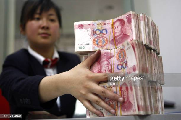 Chinese bank worker arranges stacks of 100-yuan notes at a bank in Suining, southwest China's Sichuan province on March 20, 2010. By pushing China...