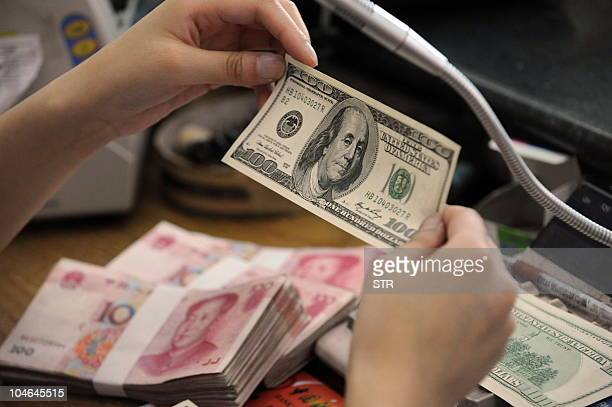 A Chinese bank worker checks a US 100dollar bill together with stacks of 100yuan notes at a bank counter in Hefei east China's Anhui province on...