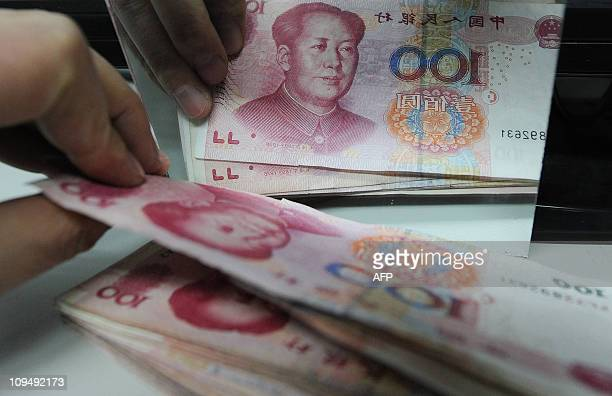 A Chinese bank worker counts a stack of 100yuan notes at a bank in Hefei east China's Anhui province on February 27 2011 A sharp rise in the Chinese...