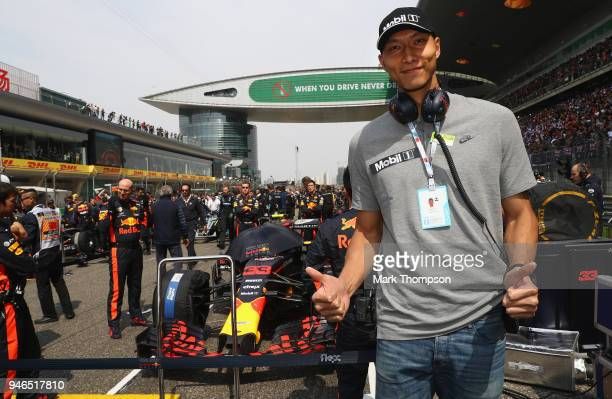 Chinese basketball player Yi Jianlian poses for a photo with the car of Max Verstappen of Netherlands and Red Bull Racing on the grid before the...