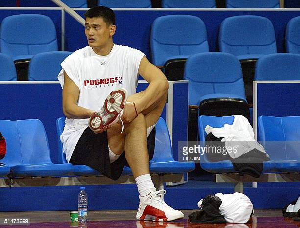 Chinese basketball star and Shanghai native Yao Ming of Houston Rockets sits on the bench during a practice session at Shanghai Stadium, 13 October...