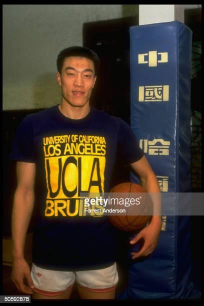 Chinese basketball star Ma Jian pausing fr practice shooting proudly sporting UCLA Bruins tshirt re winning scholarship fr Amer Univ