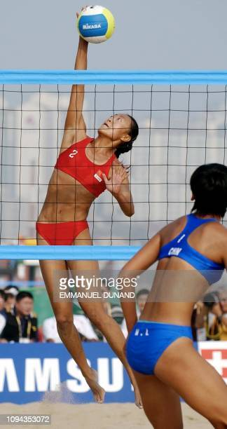 Chinese beach volleyball player from China-A team Wang Fei smashes the ball past fellow Chinese from China-B team Wang Lu 04 October 2002 during the...