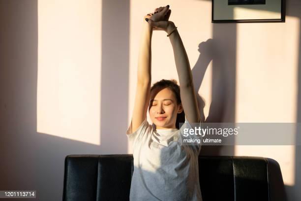 a chinese beauty stretches on the sofa - körperpflege stock-fotos und bilder