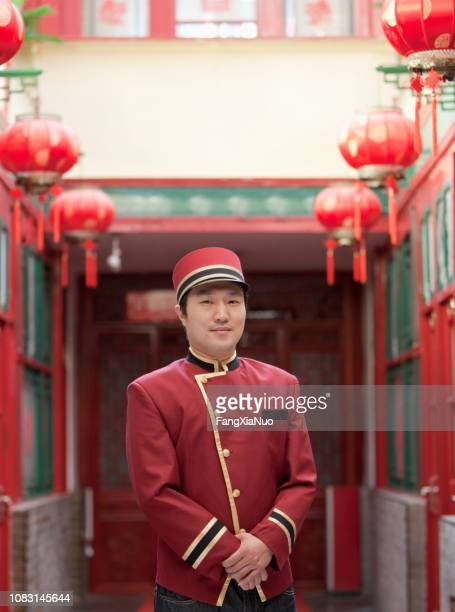 chinese bellhop standing in hotel - communication occupation stock pictures, royalty-free photos & images