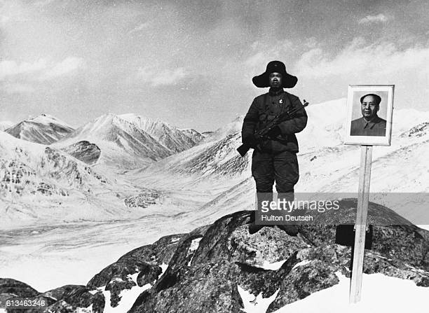 A Chinese border guard on the RussianChinese border stands next to a picture of Mao Tse Tung