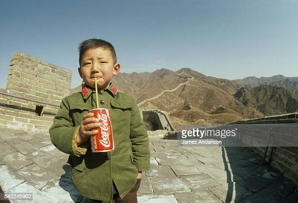 A Chinese boy drinks a can of CocaCola on the Great Wall of China