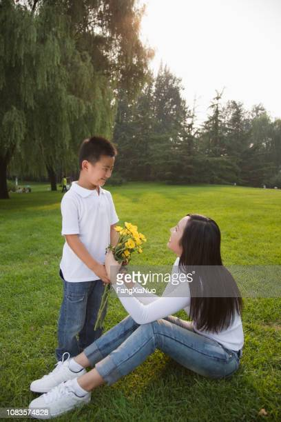 chinese boy giving mother bouquet of flowers - chinese mothers day stock pictures, royalty-free photos & images