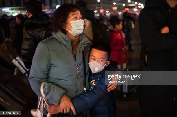 Chinese boy hugs a relative as she leaves to board a train at Beijing Railway station before the annual Spring Festival on January 21 2020 in Beijing...