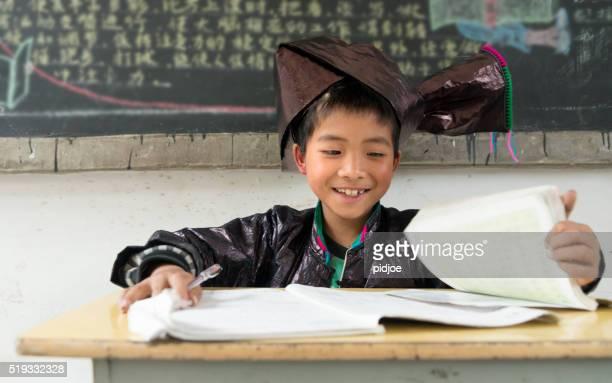 Chinesische Junge in traditioneller Kleidung, die an der Schule-Dong