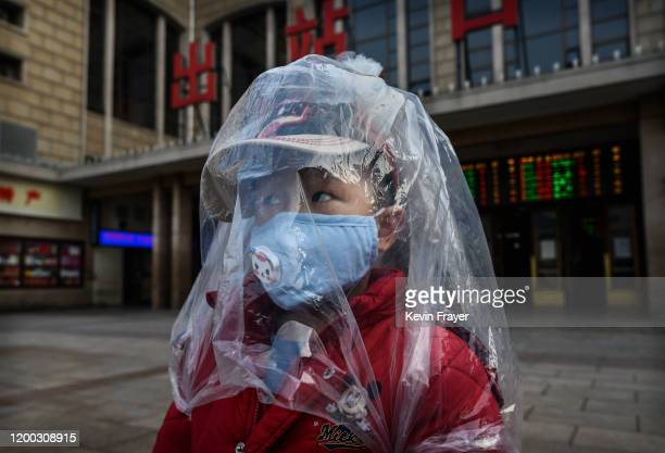 Chinese boy is covered in a plastic bag for protection as he arrives from a train at Beijing Station on February 12 2020 in Beijing China The number...