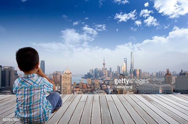 Chinese boy looking at  the  Shanghai skyline from high position