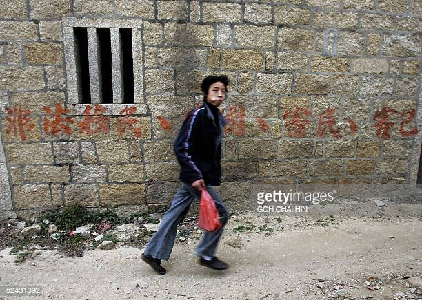 Chinese boy passes by one of the many handwritten advertisements offering wellpaid overseas jobs outside village homes in the isolated Pingjiao Ziran...