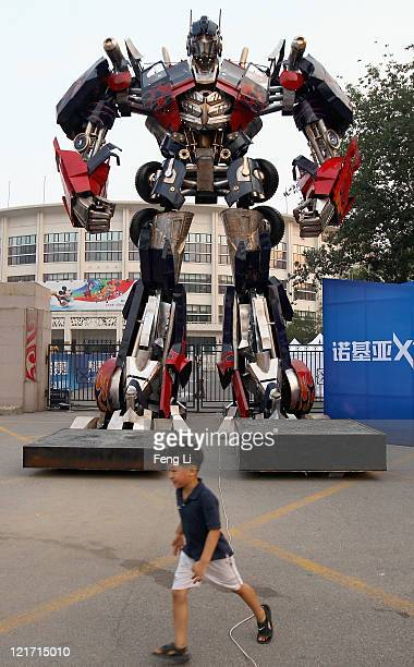Chinese boy passes by the transformer model Optimus Prime displayed for a promotion outside Beijing Workers' Gymnasium on August 22 2011 in Beijing...