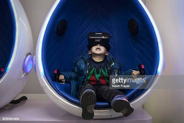 Chinese boy reacts while wearing virtual reality glasses in a roller coaster simulator at Leke VR Park a leading chain on November 26 2016 in Beijing...
