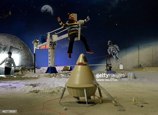 A Chinese boy rides a zero gravity device at the Science Museum in Beijing December 1 2013 China's state media and people eagerly awaited the launch...