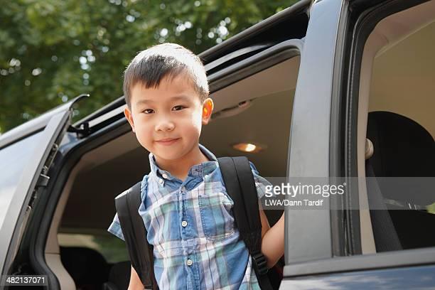 Chinese boy standing in car doorway