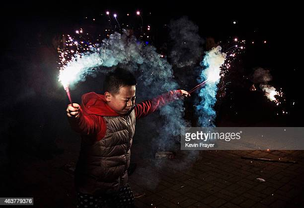 A Chinese boy uses sparklers during celebrations of the Lunar New early on February 19 2015 in Beijing ChinaThe Chinese Lunar New Year of Sheep also...