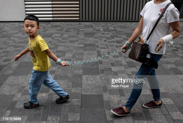 Chinese boy wears a leash attached to his wrist while walking with his guardian at a local shopping mall on September 11 2019 in Beijing China
