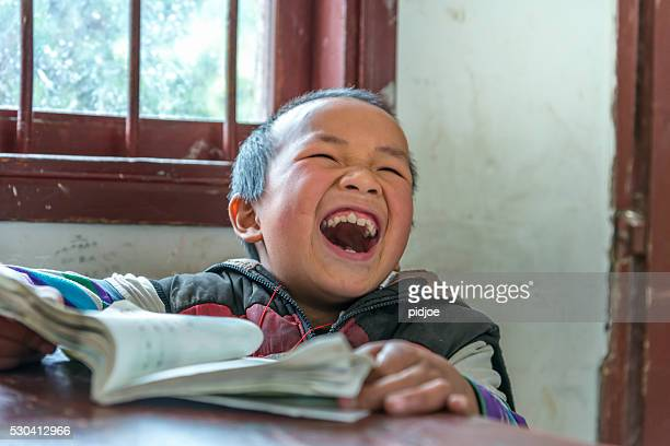Chinese Boy with big laugh at school,looking away