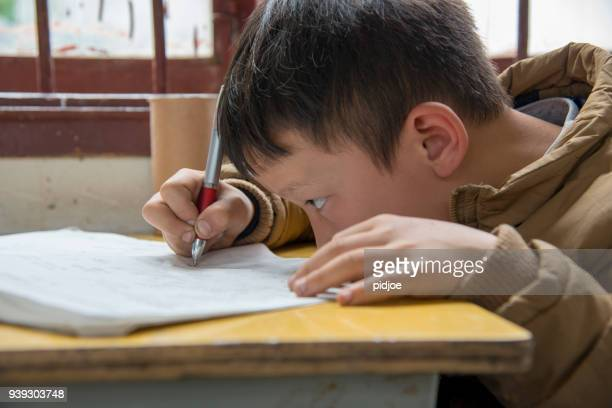 chinese boy working at school, highly concentrated in small dong village, huang gang,facial portrait of a chinese schoolboy,. the boy holding a pen is writing at school. huang gang, small dong village in guizhou, china. - one boy only stock pictures, royalty-free photos & images