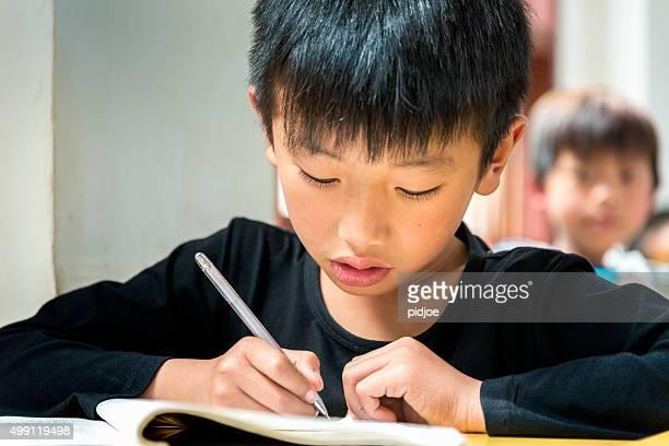 chinesische junge bei der arbeit in der schule, hochkonzentrierte - schulkind nur jungen stock-fotos und bilder