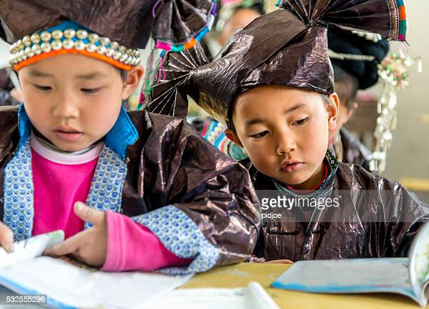 Chinese Boys in Traditional Dong Clothing working at school