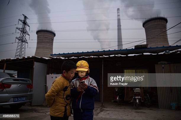 Chinese boys look at their smartphone in front of their house next to a coal fired power plant on November 27 2015 on the outskirts of Beijing China...