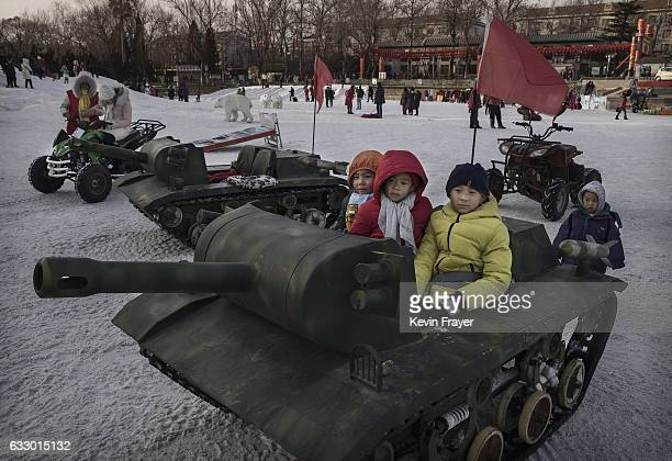 Chinese boys sit in a motorized toy tank at a fair on the second day of the Chinese Lunar New Year on January 29 2017 in Beijing China China is...