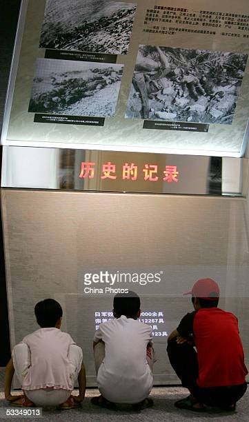 Chinese boys view drawings and pictures from the 1937 Nanjing Massacre during an exhibition of historical facts on the massacre at the National...