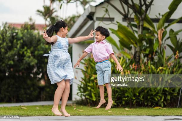 Chinese brother and sister jumping in the front yard
