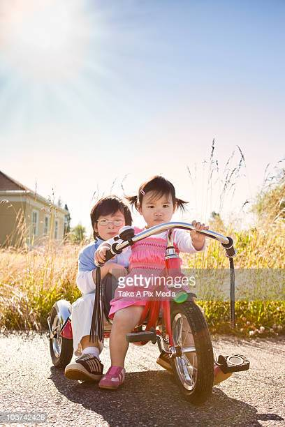 Chinese brother and sister riding tricycle