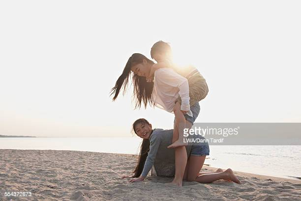 Chinese brother and sisters playing on beach