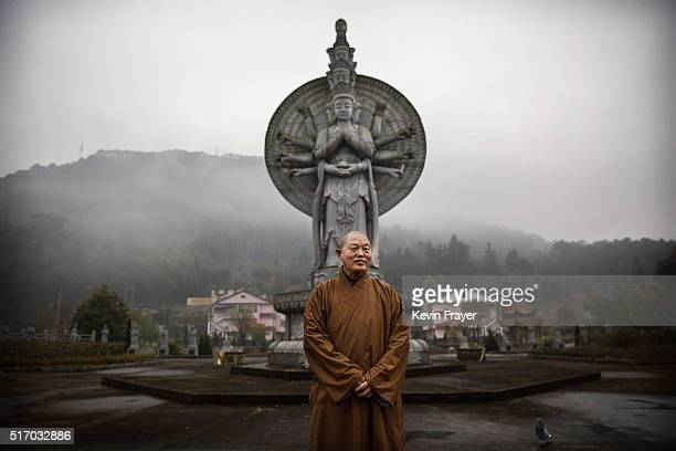 Chinese buddhist monk Dao Yuan stands in front of a statue of the Buddha at the Ji Xiang Temple and nursing home on March 17 2016 in Sha County...