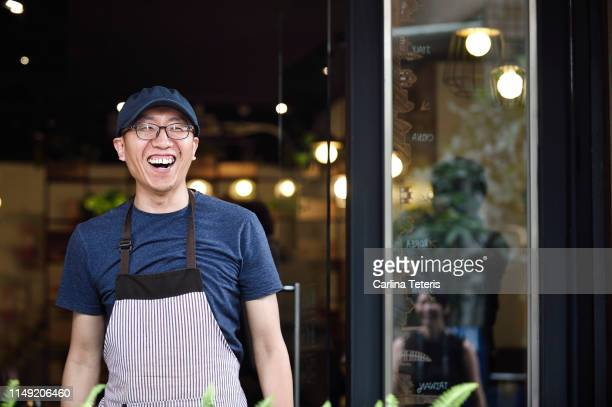 chinese business owner standing in front of his cafe - owner stock pictures, royalty-free photos & images