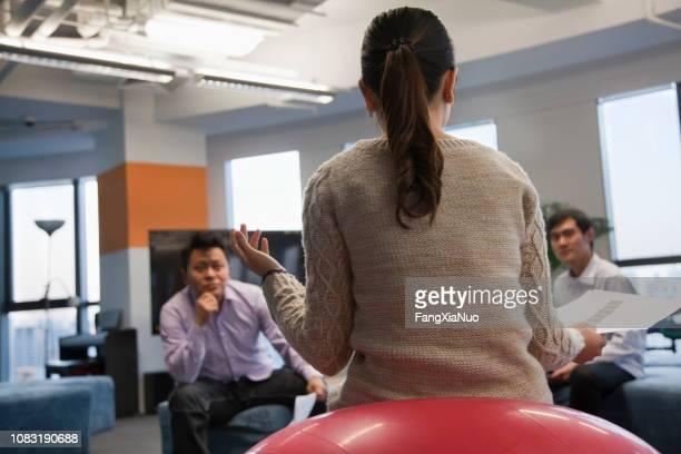 事務所で話している中国の実業家 - 後ろで束ねた髪 ストックフォトと画像