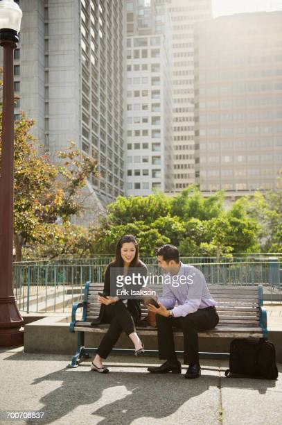 Chinese business people using technology on city bench