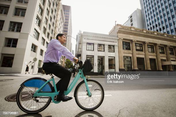 Chinese businessman commuting on bicycle in city