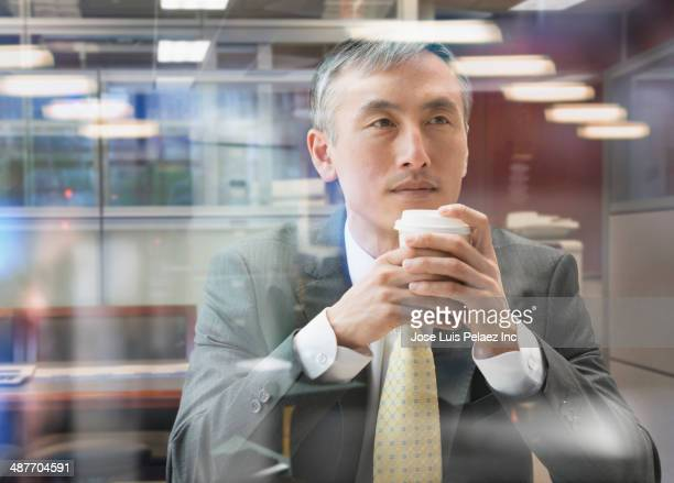 Chinese businessman drinking cup of coffee at window