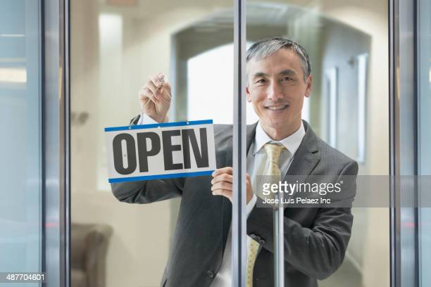 Chinese businessman hanging Open sign in window
