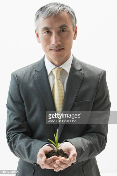 Chinese businessman holding seedling