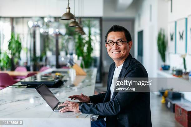 chinese businessman in contemporary cafe using laptop - asia stock pictures, royalty-free photos & images