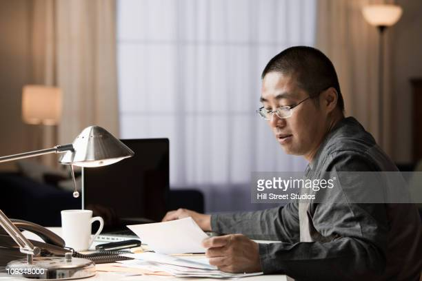 Chinese businessman looking at mail at desk